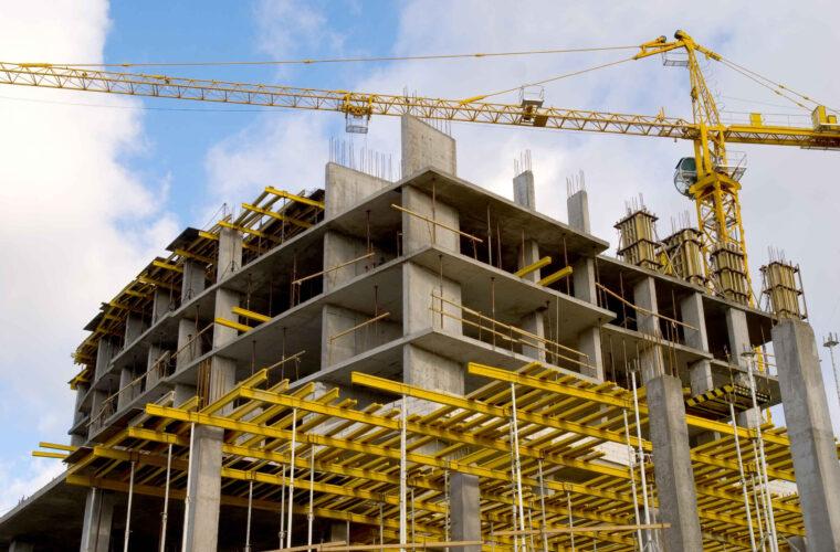 crane near building on cloudly sky background